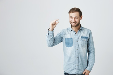 Positive bearded man has trendy hairstyle, wears denim shirt, smiles at camera shows something small. Happy stylish man shows size of gift box. Body language concept