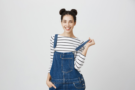 Playful positive carefree brunette female with two hairbuns with joyful smile, has cheerful expression, wears denim overalls, plays with straps, rejoices weekends, poses against gray background. Foto de archivo