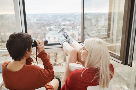 Back portrait of hot attractive women sitting on balcony with legs leaned on window, using binocular and drinking coffee. Girls fool around and spy after their neighbors or enjoy scenery of their town