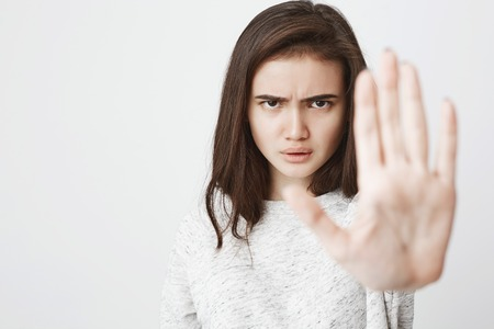 Portrait of beautiful european woman with serious and angry expression stretching one hand in hold or stop gesture, over white background. Girl is at cosplay party saying you shall not pass