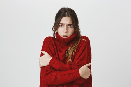 Waist-up portrait of girl suffering from physical discomfort because of fever. Dark-haired woman with ponytail dressed in red loose sweater feels cold in winter Stock Photo