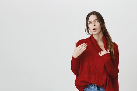 Waist portrait of sick ill dark-haired female dressed in red sweater and jeans. Girl suffering from physical discomfort because of fever. Woman has a weakened immune system or other medical problems Stock Photo