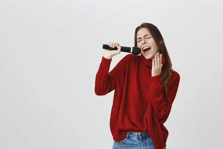 Waist-up portrait of funny young European girl with ponytail wearing casual clothes enjoyes singing songs, holding microphone in her hands. Full of joy, happy female singer Stockfoto