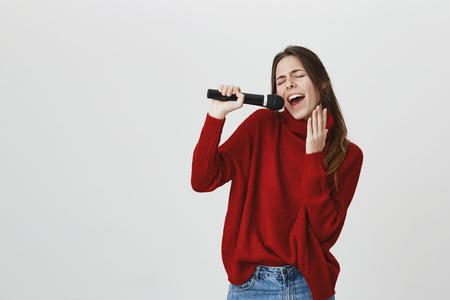 O retrato da cintura-acima da menina européia nova engraçada com o rabo de cavalo que veste a roupa ocasional aprecia cantar canções, prendendo o microfone em suas mãos. Cheio de alegria, feliz cantora Foto de archivo