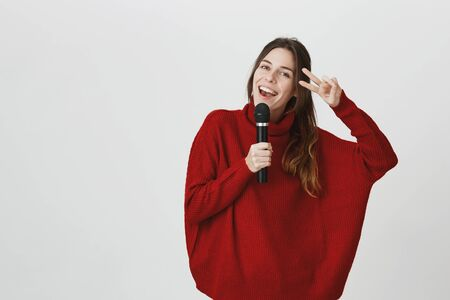Talented female model in loose red sweater holding microphone and singing songs while posing against gray background. Girl-singer smiling joyfully and showing v sign. Positive emotions and gestures