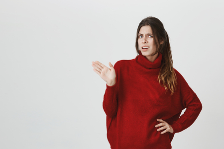 Waist-up portrait of young woman in red loose sweater with dark hair, frowning her face, standing against gray wall with copy space, showing opened palm, expressing her dissatisfaction and dislike