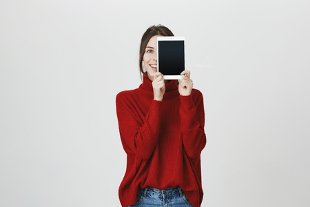 Advertising concept. Shot of joyful beautiful dark-haired young woman holding in her hands modern tablet computer and standing against gray background with joyful smile. Girl motivating customers