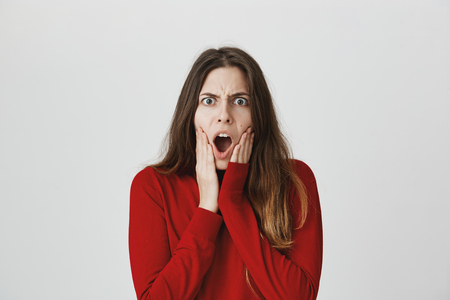 Portrait of attractive european girl holding hands on face, expressing shock, imitating scream picture, isolated over white background. It is her favorite peace of art. Represents all her mood Reklamní fotografie