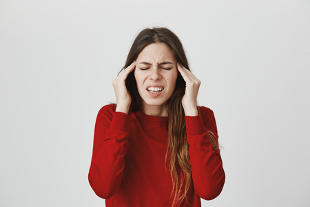 Stressed frustrated young female dressed in red sweater with closed eyes, frowns face, holds hands on temples, suffers from headache, feels annoyed and bored because of noise and useless information 免版税图像 - 94340536
