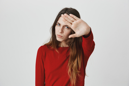 Body language. Stressed out serious angry young woman with straight dark hair posing against studio wall, keeping hand in stop gesture, trying to defend herself as if saying: Stay away from me