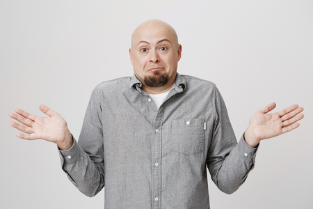 Studio shot of emotional clueless bald man dressed in gray shirt over white t-shirt having confused puzzled look, frowning face, shrugging shoulders as he doesnt know reason of accident Stock Photo