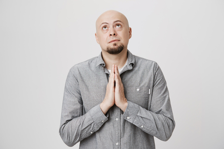 Portrait of caucasian bald bearded male keeps palms together, has pleading expression, asks for fortune, looks upwards with great desire. Baldheaded man dressed casually praying Stock Photo