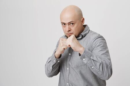 Fierce and confident stylish european bald bearded male model in gray shirt holding fists in front of him as if ready for fight or any challenge, pursuing lips, having determined expression on face
