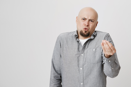 Horizontal portrait of dissatisfied and displeased bald man with beard dressed casually, gesturing actively, frowning face while arguing with his wife. Hairless male pouting lips in resentment Stock Photo