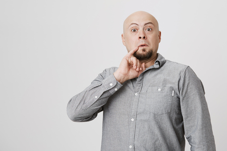 Studio shot of bald bearded man in gray shirt poses against gray background, holds little finger behind corner of his mouth, looks like Dr. Evil. Hairless male grimacing and making faces indoors Stock Photo