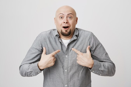 Shot of stunned bald bearded man with opened mouth in shock, being accused of something he didn`t make, pointing with index fingers at himself. Face expression and negative emotions