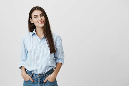 Successful young smiling european woman with hands in pockets, wearing office shirt and jeans while standing over gray background. Director discusses something with employees