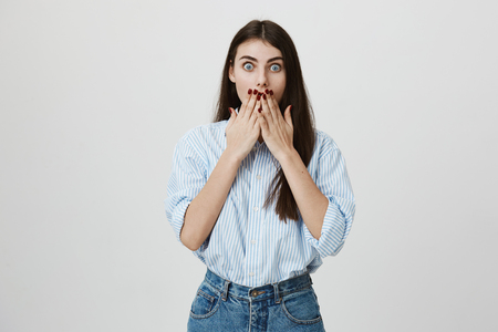 Portrait of nice and cute european student, covering mouth with hands, expressing shock and surprise with widened eyes, standing over gray background. Woman heard unbelievable news from her mother. Stock Photo