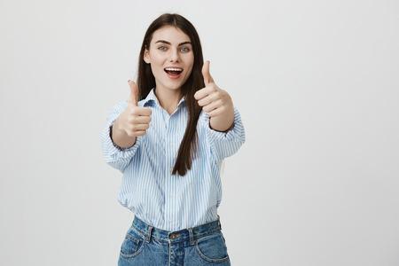 Retrato de exitosa joven empresaria, estirando las manos con los pulgares hacia arriba, expresando satisfacción y aprobación, de pie sobre fondo gris. Mujer muestra su alegría y respuesta positiva.