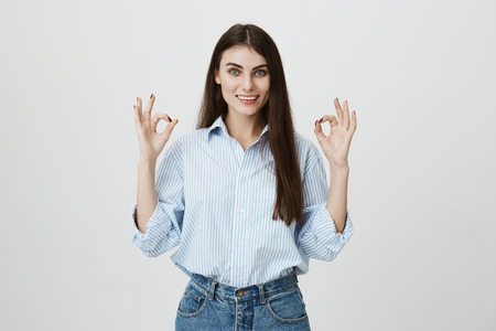 Attractive young european female student in blue shirt and jeans, showing okay or fine gesture while smiling broadly and standing over gray background. I definitely approve your idea to visit bar Stok Fotoğraf - 94388723