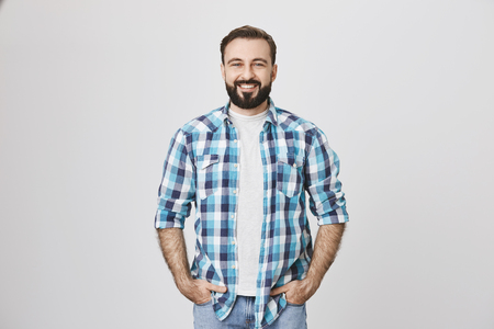 Portrait of stylish bearded guy in plaid shirt smiling broadly while holding hands in pockets, over gray background. Man at building store buy stuff to make repairment works at home Stock Photo