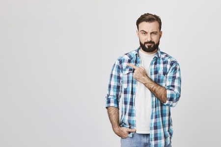 Portrait of suspicious bearded man pointing left with one hand and looking at camera, standing over gray background. Guy who went on date with girl from social network not sure it was her true photos Reklamní fotografie