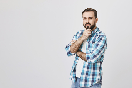 Studio shot of half-turned handsome man with beard and moustache, crossing one hand and touching chin with another, expressing interest and curiosity, over gray background.