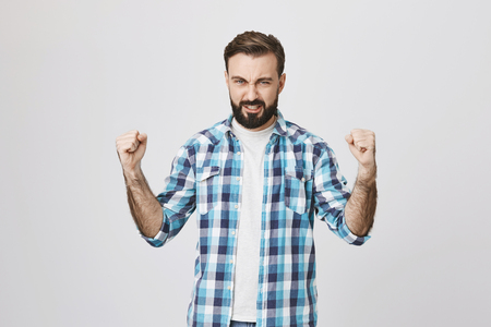 Portrait of handsome athletic adult male showing power and muscles while wearing plaid shirt, standing over gray background. Husband shows wife he can handle everything and fix shower on his own Stock Photo