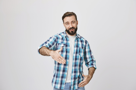 Funny adult bearded man with trendy haircut and plaid shirt making robot gestures or reading rap standing over gray background. Man tries to impress woman with modern poetry.