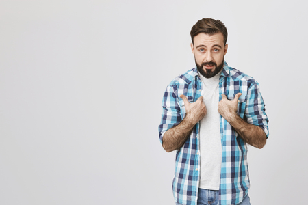 Studio shot of bearded european person pointing at himself with offended expression, standing against gray background. Guy feels mad because his girlfriend blames him for every disaster that happens Stock Photo