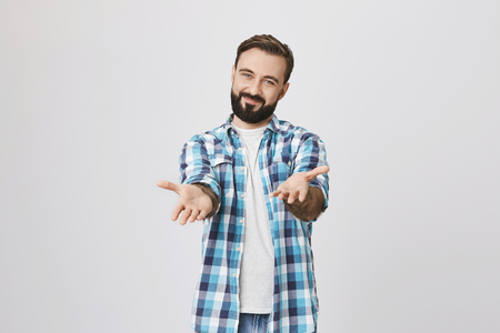 Cute bearded ault man, wearing blue checked shirt, spreading hands against him, while looking with nice smile at camera, over gray background. Please come in dear friends gesture.
