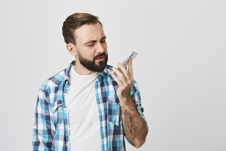 Portrait of attractive european man with stylish haircut and beard looking at smartphone with confusion while holding it in arm, over gray background. Car stuck in countryside where is no connection