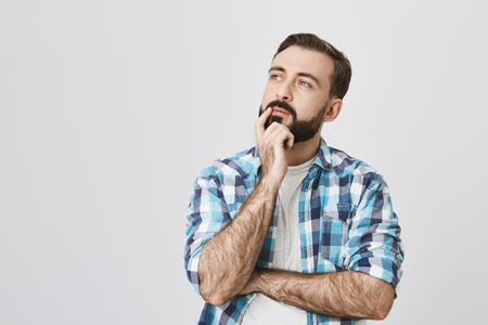 Idea and thought concept. Curious man with beard and stylish haircut standing over gray background in thoughtful pose and half-turned face, looking aside. Guy thinks what he should order
