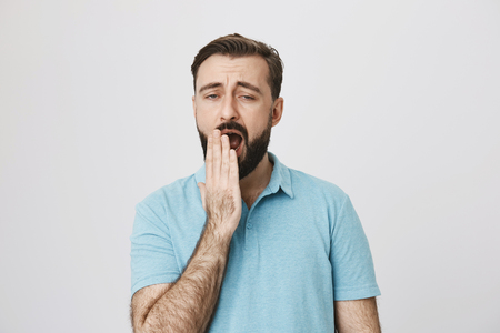 Tired bearded man in blue t-shirt yawning and covering mouth with hand, standing over gray background. Man who works night shift have not slept at all dreaming only about warm bed and pillow