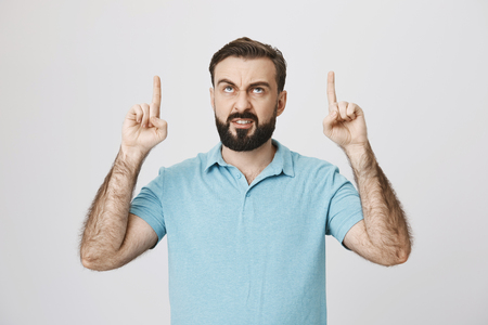 Indoor portrait of angry european bearded male pointing up with index fingers and gloomy smile, over gray background. Man hate his annoying neighbors who always yell at midnight