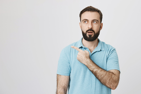 Picture of a mature bearded man looking amazed and shocked pointing away over white background. Person was in the middle of conversation when he saw something really terrifying. Stock Photo