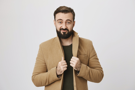 Portrait of a middle aged man with a confident expression wearing a coat over a white background. Handsome guy is looking at the mirror before going out. He sure thinks he is the best.