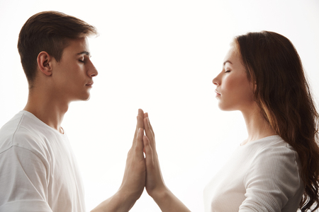 Young couple in love holding hands with their eyes closed. She took her boyfriend do yoga and it worked well for their relationship. Looks like they can feel each other without saying a word. Imagens
