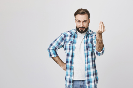 Attractive caucasian guy looking mad and angry, holding hand on waist while showing get to the point gesture with another, over gray background. Furious landlord says time is up and want his money Stock Photo