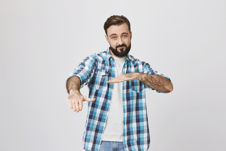 Attractive adult bearded husband in plaid shirt dancing hip hop showing yo gesture with hands, standing against gray wall. Dad tries convince teenage daughter he knows what is in trend Stock Photo