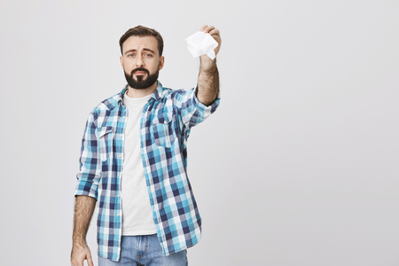 Indoor shot of gloomy sad bearded adult man holding tissue in hand and waving it like saying goodbye, standing over gray background. Father send off daughter to summer camp for the first time. Archivio Fotografico