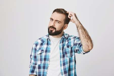 Portrait of european bearded man with puzzled emotions, scretching his head, expressing that he is clueless, over gray background. Guy opened refrigerator and do not remember what he wanted to get 写真素材
