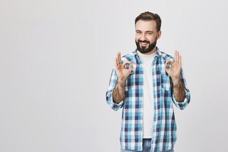 Portrait of happy handsome bearded male saying everything is okay and fine with gesture, standing over gray background. Hey, I got it, everything will be done perfectly