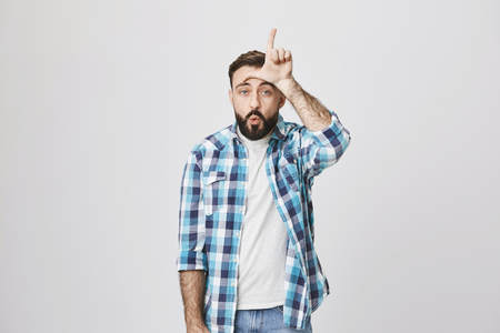 Funny caucasian male with beard and moustache makes fun of somebody, holding hand on forehead with loser gesture and folded lips, standing against gray background. Guy triumphs over his rival Фото со стока