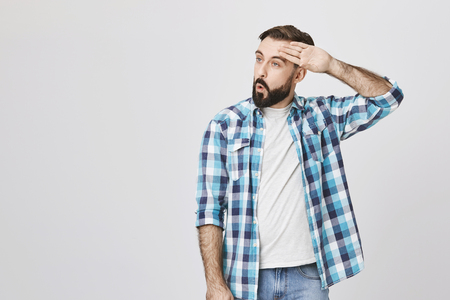 Adult bearded guy wiping his forehead with hand making phew gesture, expressing relief while standing against gray wall. Man feels happy that he prevented huge disaster. It was close enough