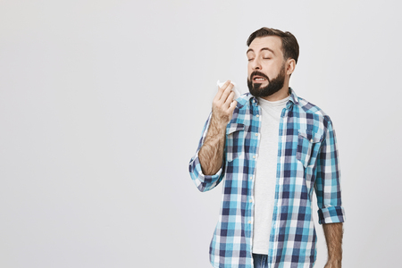 Studio shot of sick man who is about to sneeze with closed eyes and opened mouth while holding napkin in hand, standing over gray background. Friend has cat and this guy is allegic to it.