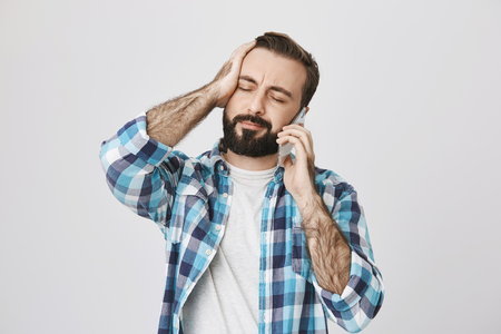 Portrait of tired and perplexed young adult with beard and moustache closing eyes and holding hand on head while talking on smartphone, over gray background. Worker forgot about his shift Stockfoto