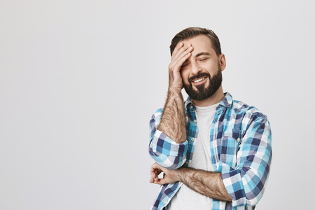 Studio shot of handsome bearded man in checked shirt, holding hand on forehead while smiling, expressing positive emotions, over gray background. Oh, I totally forgot about that hilarious moment