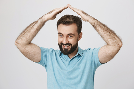 Smiling handsome man with a beard lifts his hands above head while standing near white wall. Gesture and emotions concept. Person do not want to do something he was asked to, so he says pass