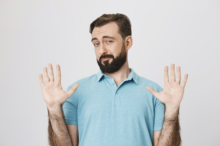 Portrait of handsome european bearded man, raising hands in surrender gesture, smiling and looking uncertain, standing over gray background. Fine, you won, I am out of this